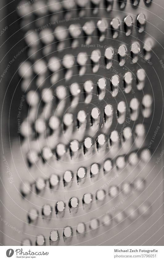 detaillierte monochrome Makroaufnahme einer Metall-Käsereibe Klinge Koch Schuss rechteckig Essen zubereiten Diät Küche vorbei reiben glänzend Küchenchef retro