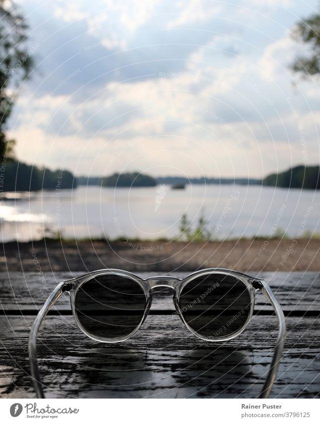 Wunderschöner See hinter einer Sonnenbrille gesehen Accessoire Hintergrund Textfreiraum Brille durch eine Sonnenbrille schauen persönliche Perspektive