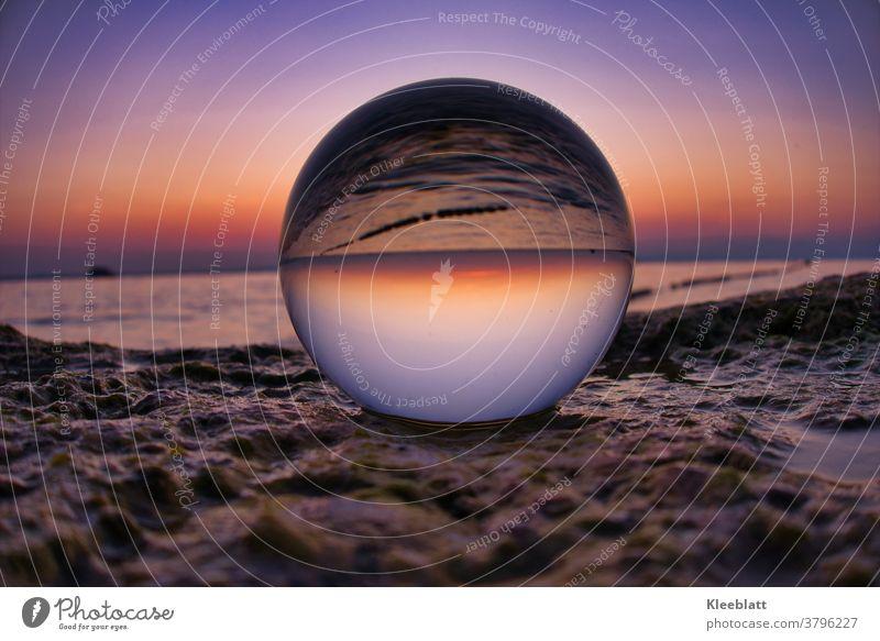 Glaskugel auf einer Felsplatte, die bei Sonnenuntergang das schöne Wasser und Licht des Sees reflektiert Sonnenenuntergang Außenaufnahme Kugel