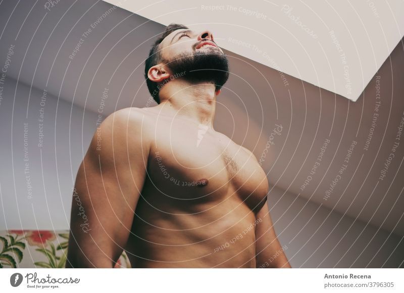 34 Jahre alter Mann am Fenster stark Licht Torso aufschauend ohne Hemd Deckenbeleuchtung Männer 30s männlich Erwachsener Lifestyle Person Menschen bärtig