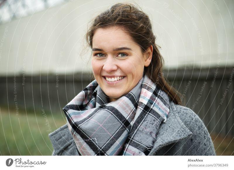 Nahes Portrait einer jungen Frau mit Grübchen, die draußen vor einem Gebäude steht junge Frau 18-25 Jahre Lächeln Freude warmherzig schön charmant schlank