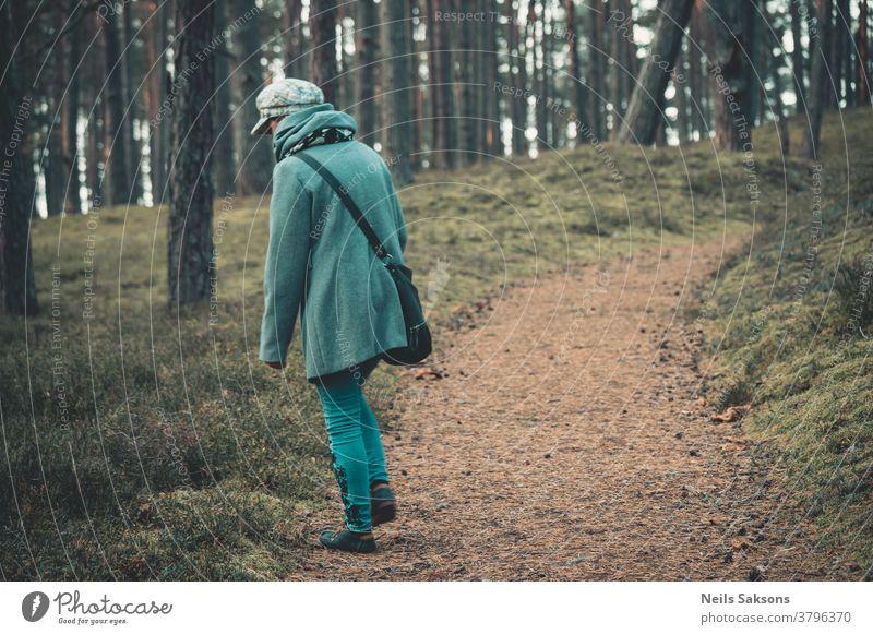Frau, die in den Wäldern nahe der Ostsee spazieren geht Mantel Hut blau grün Wald nadelhaltig Kiefern Kiefernzapfen Kiefernadeln Nachlauf Weg Serpentinen