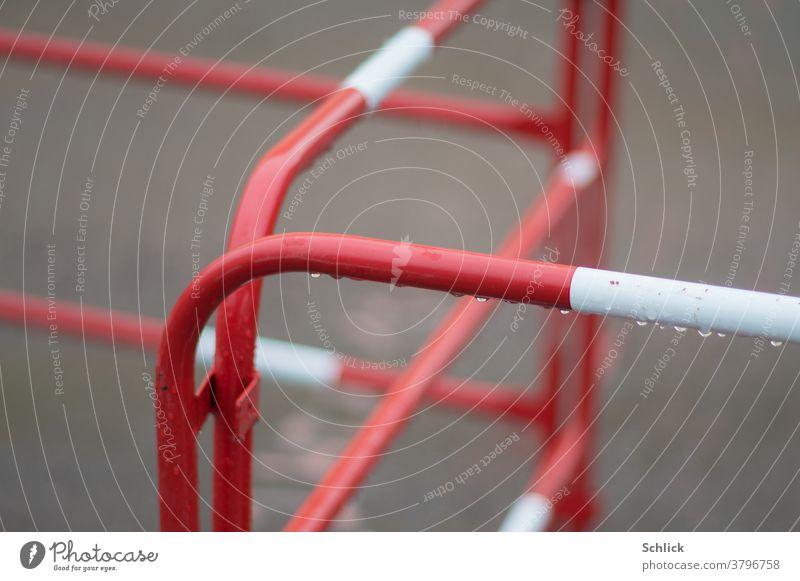 Baustellenabsperrung in rot und weiß kreuz und quer Absperrung Metall geringe Tiefenschärfe Regenwetter Wassertropfen Asphalt Unschärfe Metallrohr Zickzack