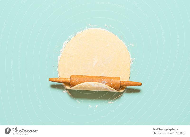 Teig ausgerollt auf grünem Hintergrund. Hausgemachte Kuchenkruste und Nudelholz. Konzept Backen obere Ansicht backen Bäckerei Backschritte Butter Butterteig