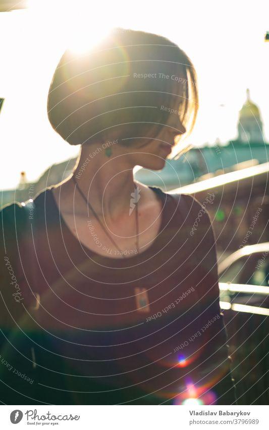Mädchen steht mit gedrehtem Kopf im Gegenlicht urban Wochenende Sonne Blendeneffekt Sonnenlicht Blendenfleck Glück Tag Sonnenstrahlen Licht Unschärfe Sommer