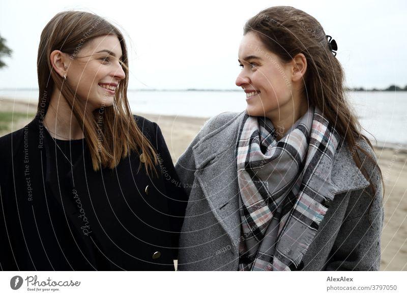 Portrait zwei junger Frauen -  Freundinnen - am Elbstrand junge Frau 18-25 Jahre warmherzig schön charmant schlank brünett lange Haare frisch groß smart