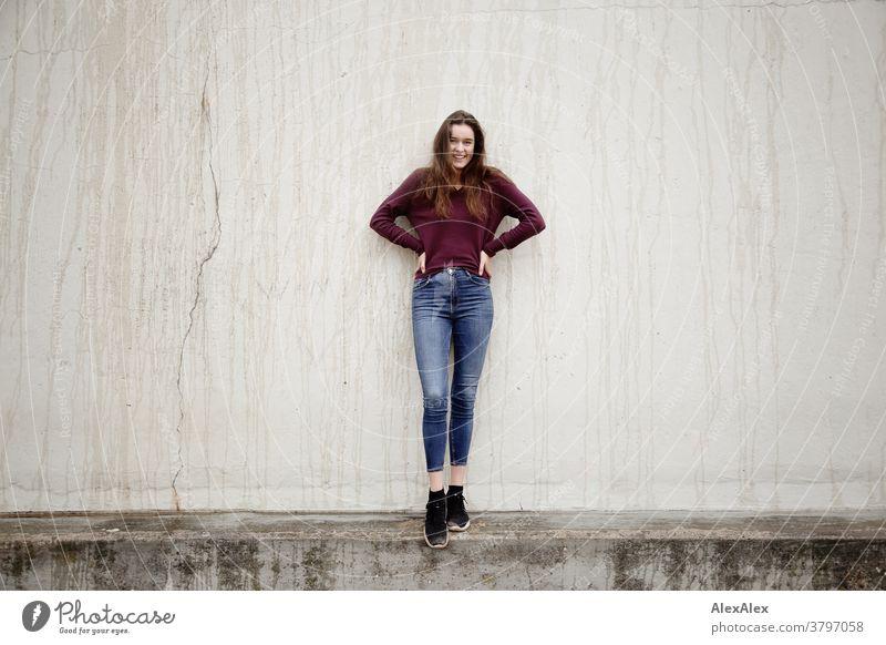Portrait einer jungen Frau die vor einer Betonwand auf einer Mauer steht junge Frau 18-25 Jahre warmherzig schön charmant schlank brünett lange Haare frisch