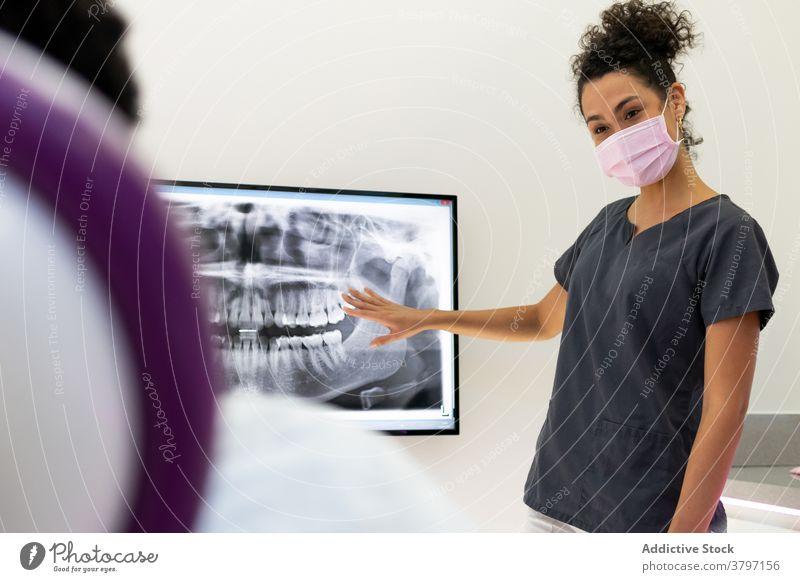 Ethnischer weiblicher Zahnarzt im medizinischen Raum mit Röntgenstrahlen Röntgenbild dental Klinik Arzt Frau Zahnmedizin Zähne geduldig Kiefer ethnisch schwarz
