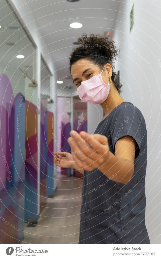 Sliming weiblichen Arzt zeigt kommen auf Geste in der Klinik komm schon ankommen gestikulieren Frau freundlich heiter Mundschutz Sanitäter ethnisch schwarz