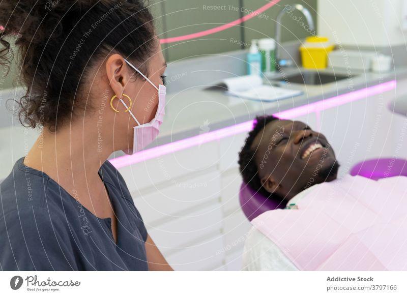 Lächelnde schwarze Zahnarzt und Patient im medizinischen Raum Arzt geduldig Leckerbissen Verfahren dental Zahnmedizin Stomatologie ethnisch Afroamerikaner