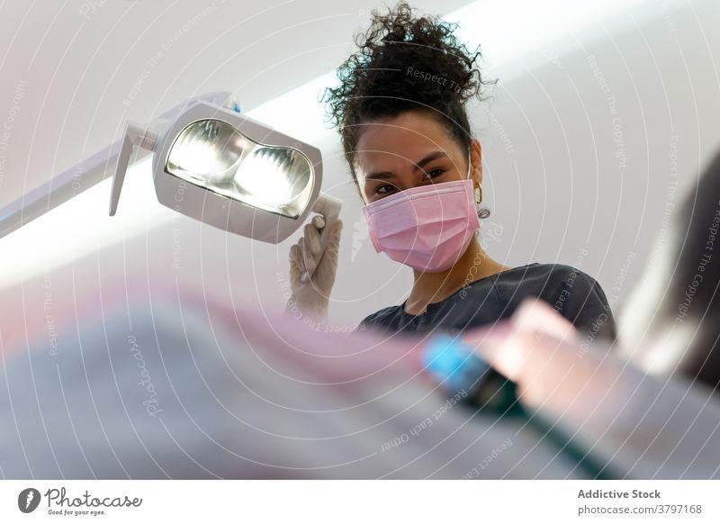 Lächelnde Zahnärztin in der Klinik dental Arzt Lampe Zahnarzt Frau vorbereiten Leckerbissen Stomatologie Licht schwarz Afroamerikaner ethnisch Gerät modern hell