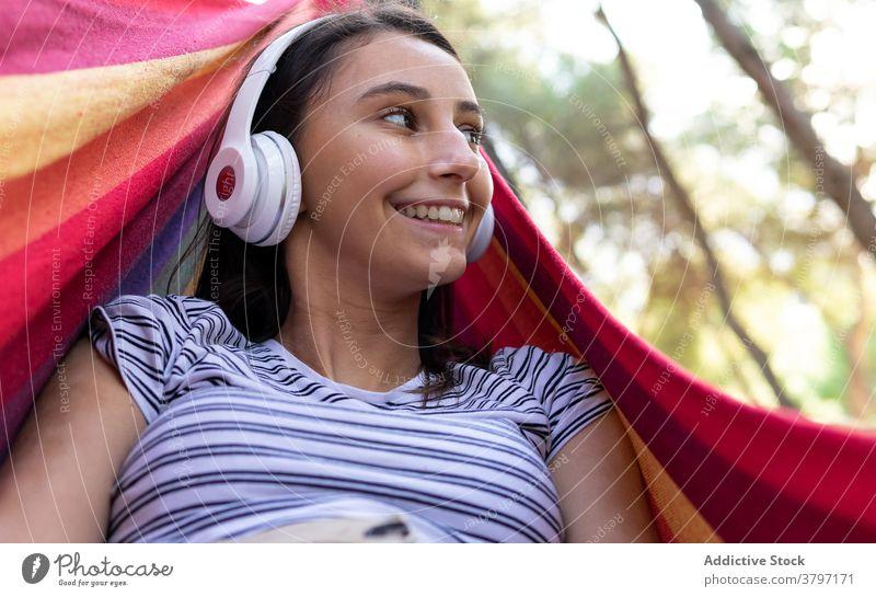 Sorglose Frau hört Musik in der Hängematte zuhören genießen hängen Park Drahtlos Melodie Windstille Kopfhörer friedlich Klang Lügen Gelassenheit Gesang Harmonie
