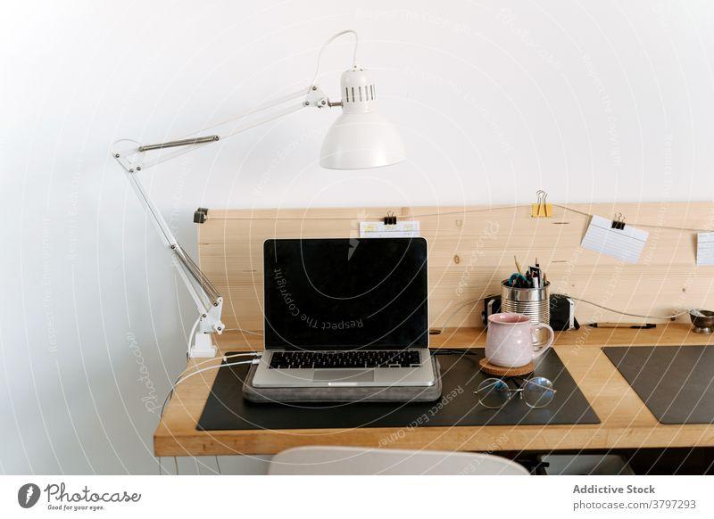 Zeitgenössischer Laptop und Brille auf Holztisch Arbeitsplatz Apparatur Büro organisieren klug modern Netbook tragbar Arbeitsbereich schwarzer Bildschirm Gerät