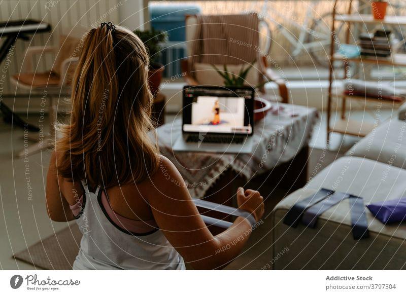 Unerkennbare Sportlerin trainiert mit Gummiband zu Hause Übung Widerstandsband Tutorial Training Vitalität Energie üben online Laptop zuschauen folgen Gerät
