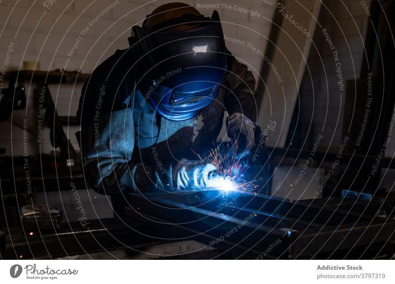 Professioneller Schweißer mit Schutzhelm in der Werkstatt Schweißnaht Metall Mann Maschine dunkel Funken Licht männlich Arbeiter Beruf professionell Werkzeug