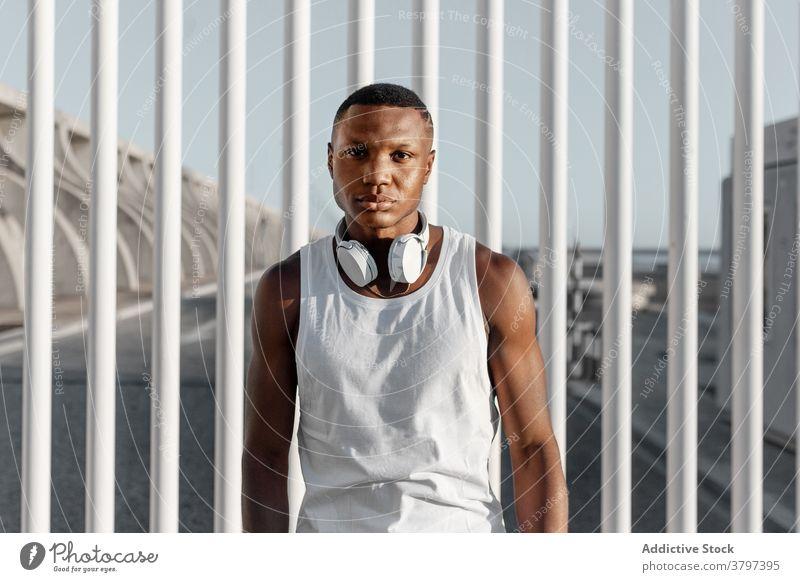Selbstbewusster schwarzer Mann steht nach dem Training am Zaun ernst selbstbewusst Sport Konzentration Fokus Muskel stark sportlich ruhen männlich muskulös