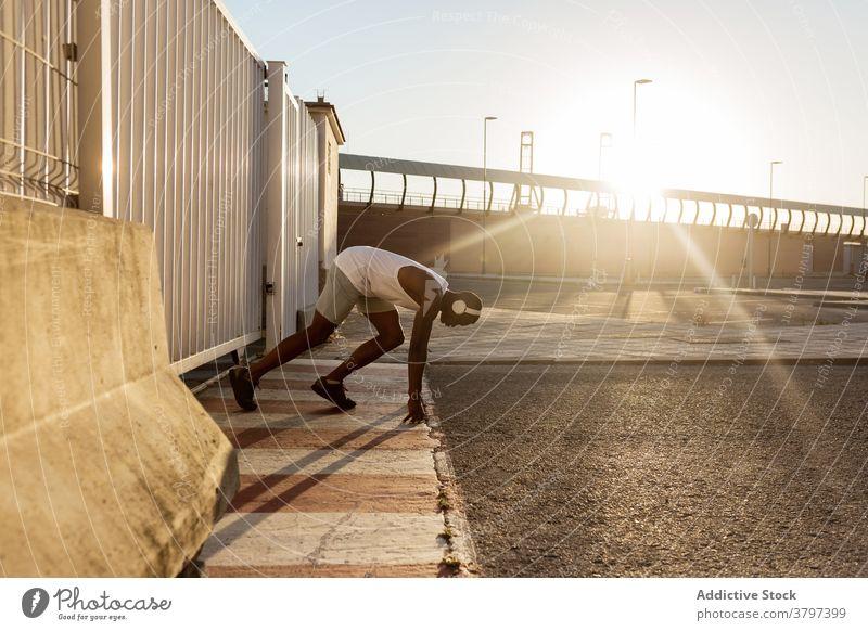 Aktiver schwarzer Sportler beim Training Start Aufwärmen Fitness Läufer Herz Übung Kopfhörer Aktivität Mann Sportbekleidung sportlich üben physisch Stärke