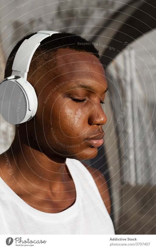 Schwarzer ernster Mann, der mit Kopfhörern Musik hört Windstille Augen geschlossen sich[Akk] entspannen Gesang Athlet zuhören Drahtlos Klang männlich ruhen