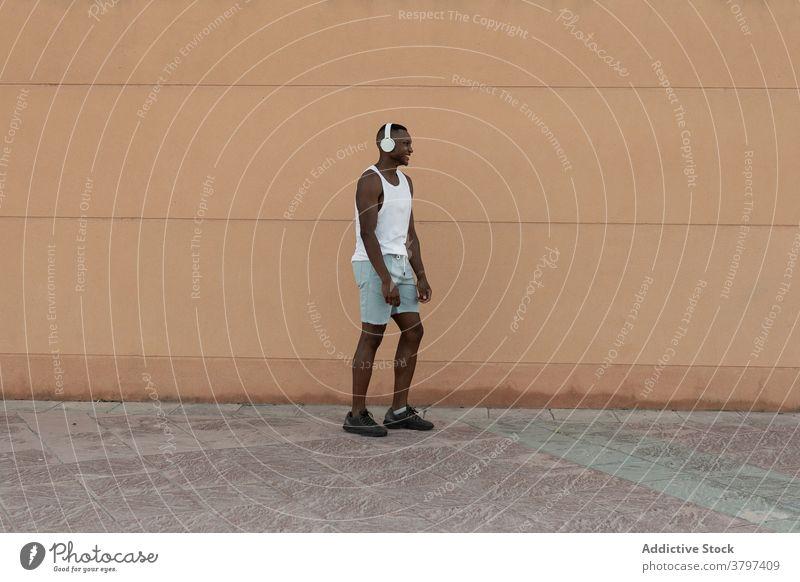 Schwarzer Sportler läuft beim Training auf der Straße Läufer Herz Aktivität Kopfhörer heiter Übung Motivation Fitness Mann Lifestyle Glück Gesundheit Lächeln