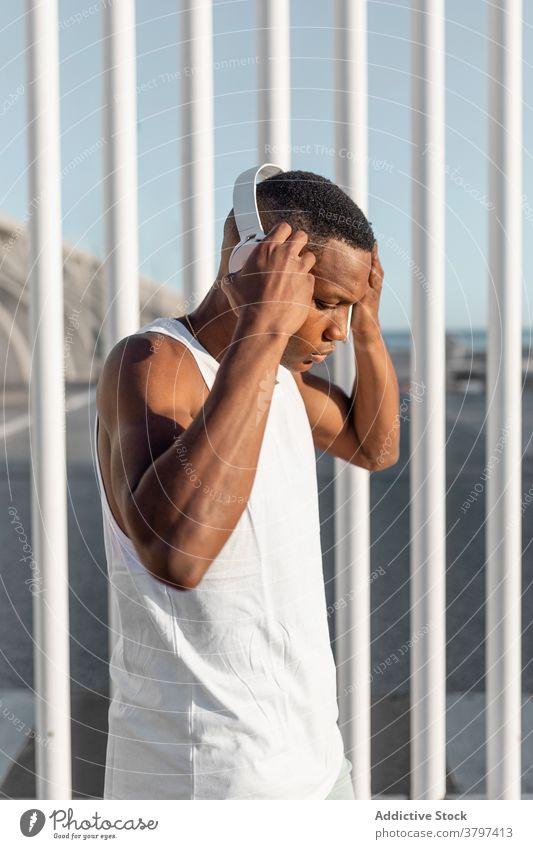 Schwarzer ernsthafter sportlicher Mann, der während des Trainings sein Smartphone benutzt Läufer Browsen benutzend Kopfhörer zuhören Athlet Pause Sportler