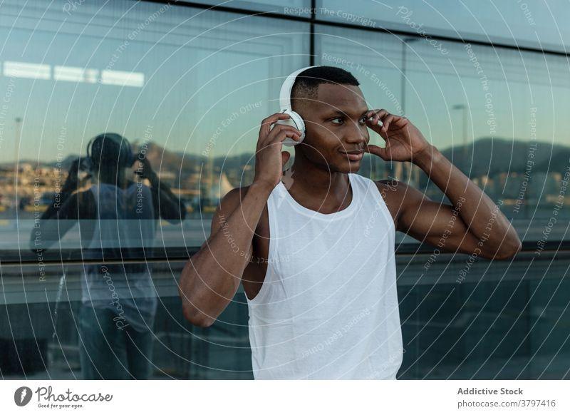 Fröhlicher schwarzer Mann, der mit Kopfhörern Musik hört heiter zuhören Freude Klang Athlet Drahtlos Optimist männlich Training Gerät Apparatur Lächeln Melodie