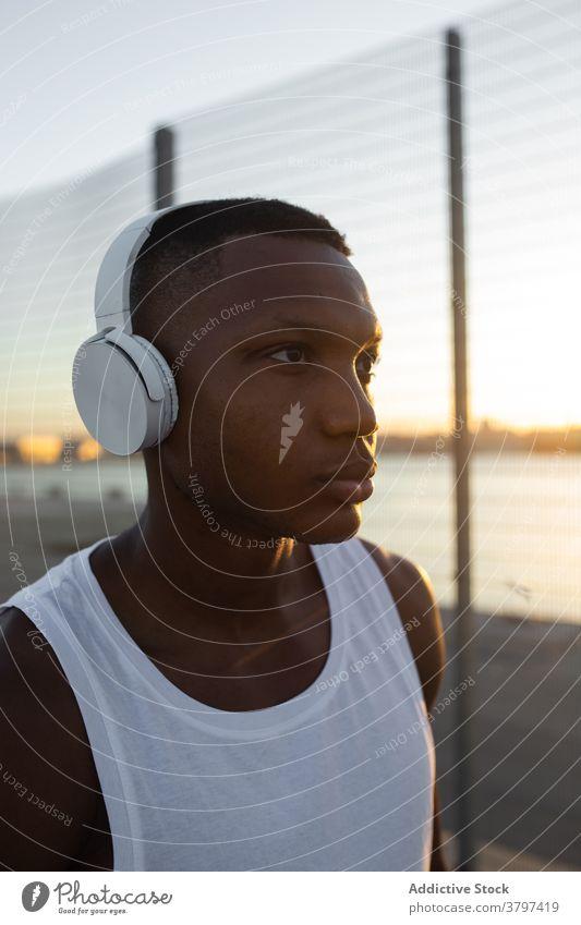 Schwarzer Sportler mit Kopfhörern beim Ausruhen nach dem Training Mann Athlet ernst muskulös sportlich Musik zuhören passen männlich Sportbekleidung Lifestyle