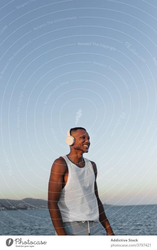 Schlanker schwarzer Mann an der Strandpromenade beim Training Läufer Lächeln Aufwärmen Kopfhörer Dehnung Energie Glück Konzentration Wohlbefinden männlich
