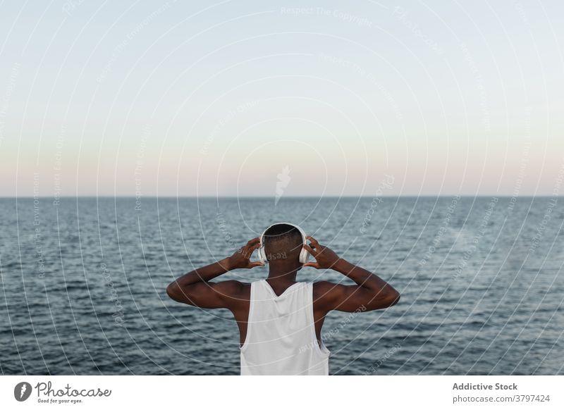 Schlanker schwarzer Mann, der sich beim Training an der Strandpromenade dehnt Läufer Hafengebiet Aufwärmen Kopfhörer Dehnung Energie Konzentration Wohlbefinden