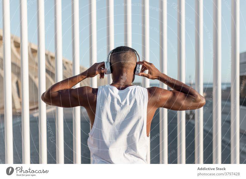 Von hinten schwarzer, sportlicher Mann, der Musik hört Läufer anonym benutzend Kopfhörer zuhören Training Athlet Pause Sportler Apparatur Sportbekleidung