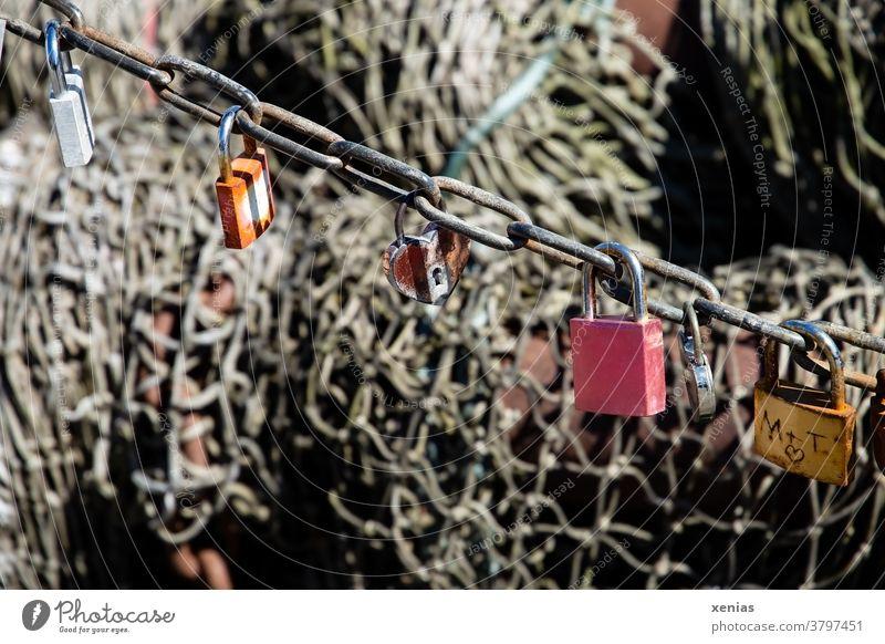 Sechs Liebes - Schlösser hängen an einer Kette vor einem Fischernetz Schloss Vorhängeschloss Verliebtheit Zusammensein Metall Gefühle Herz Rost Netz