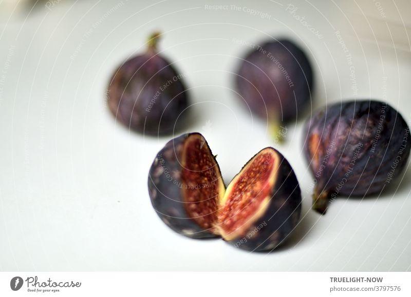 Frische, reife Feigen in dunkelblau violetter Schale, eine davon aufgeschnitten zeigt ihr rotes Fruchtfleisch, liegen auf einem weissen Tisch im hellen Tageslicht