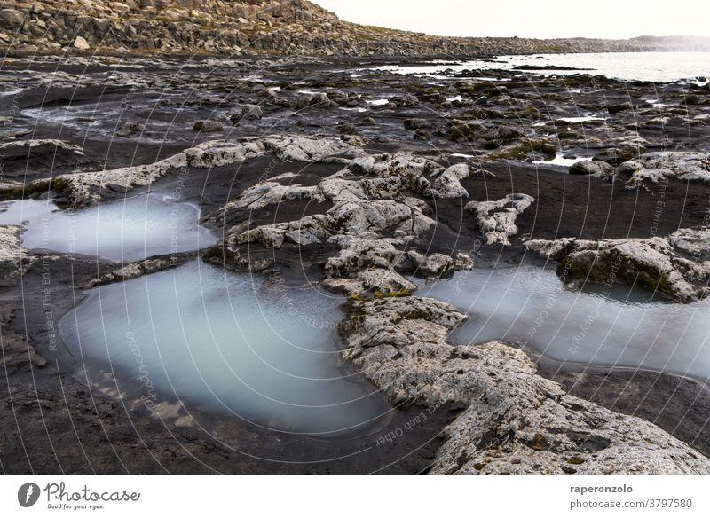 Kleine milchige Pfützen zwischen auf dem Weg neben dem Wasserfall Felsen Stein grau wandern Wanderung unwegsam sand einsam Urlaub Ferien Island