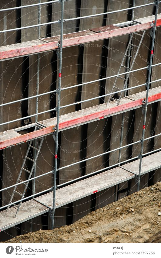 Beim Leiterspiel auf der Baustelle, schafft man mit viel Glück den Aufstieg aus der Baugrube. Über das Gerüst auf die nächste Ebene. Baugerüst Ebenen