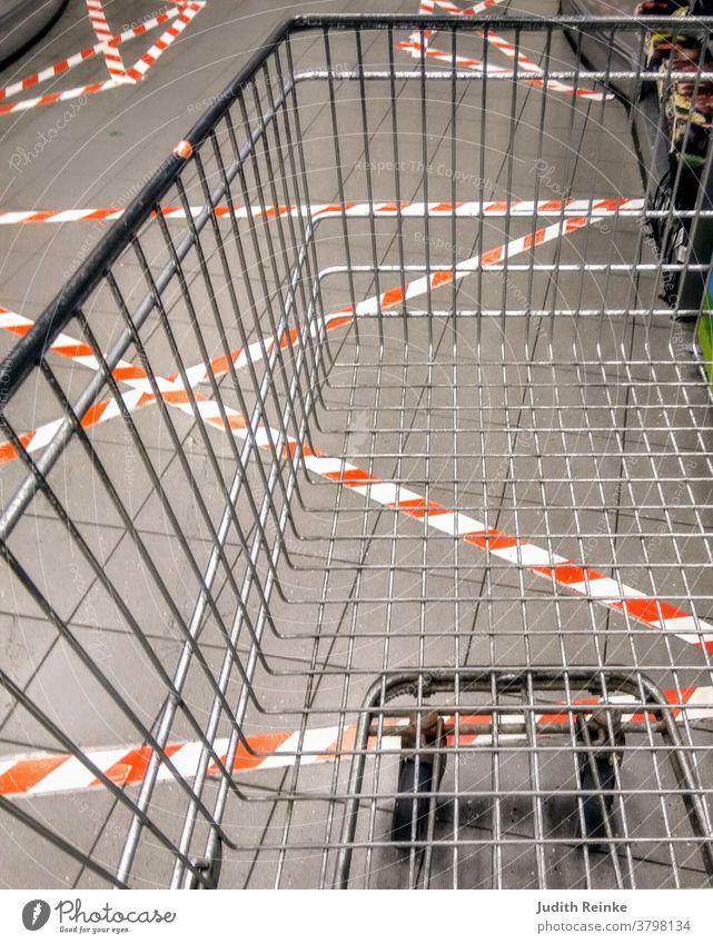 Leerer Einkaufswagen im Kassenbereich mit zig Absperrstreifen auf dem Boden geklebt | Corona | Alltagsleben während der Pandemie| Leben während der Pandemie