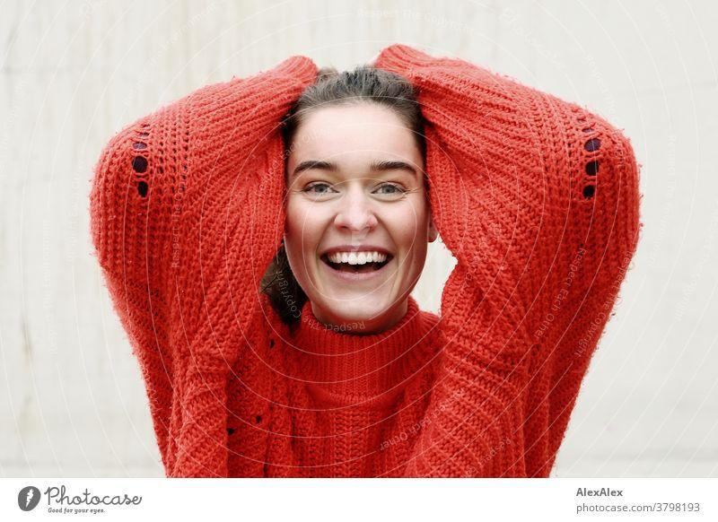 Nahes Portrait einer lachenden, jungen Frau mit Grübchen vor einer Betonwand junge Frau 18-25 Jahre warmherzig schön charmant schlank brünett lange Haare frisch