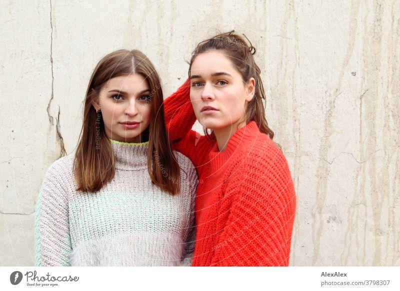 Portrait zwei jungen Frauen -  Freundinnen - vor einer Betonmauer junge Frau 18-25 Jahre warmherzig schön charmant schlank brünett lange Haare frisch groß smart