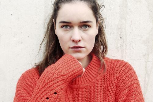 Nahes Portrait einer jungen Frau vor einer Betonwand junge Frau 18-25 Jahre warmherzig schön charmant schlank brünett lange Haare frisch groß smart emotional