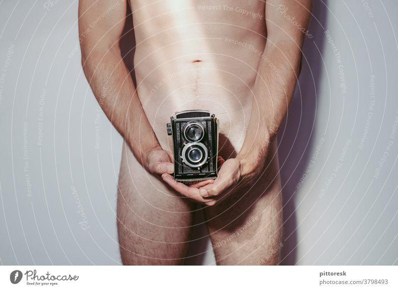 Lochkamera Junger Mann Innenaufnahme Jugendliche Selbstbewusstsein Erwachsene Mensch Medienbranche Sexualität verstecken verdecken halten Fotokamera Pornobalken