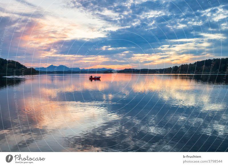 einzelnes Fischerboot am See in der Abenddämmerung Sonnenuntergang Dämmerung Silhouette Landschaft Wolken Himmel Natur Außenaufnahme Horizont Abendstimmung