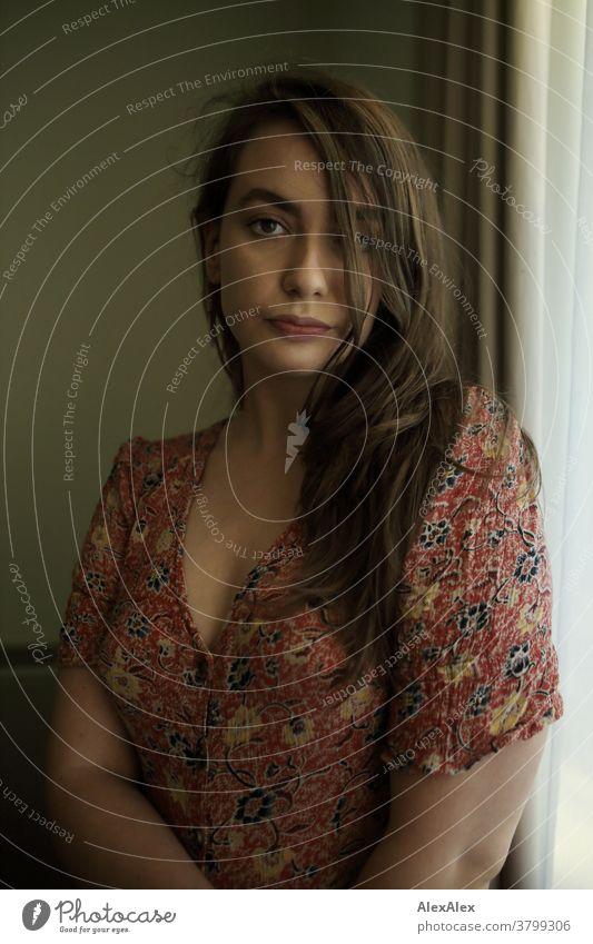 Portrait einer jungen Frau vor einem Hotelfenster schön nah fit anmutig Haut Gesicht schauen direkt langhaarig sportlich 18-30 Jahre Erwachsene Schönheit