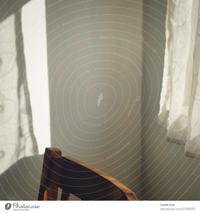 Licht und Schatten: Ein zarter Vorhang und sein Schatten an der Wand gegenüber, dazwischen ein altmodischer Stuhlrücken aus Holz Sonnenlicht Fenster Gardine
