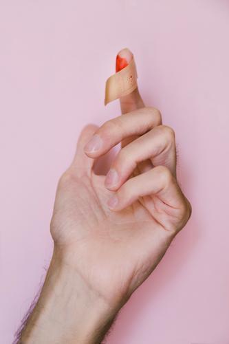 Blutiger Finger mit Fleck auf rosa Hintergrund Hand Farbfoto rot Hintergrund neutral wehtun Wunde Haut Schmerz Detailaufnahme Pflege Gesundheitswesen Medikament