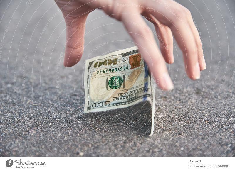 Heben Sie eine Hundert-Dollar-Banknote vom Boden auf. Konzept des gefundenen Geldes verirrt finden Straße im Freien Bürgersteig Person Tropfen Bargeld Rechnung