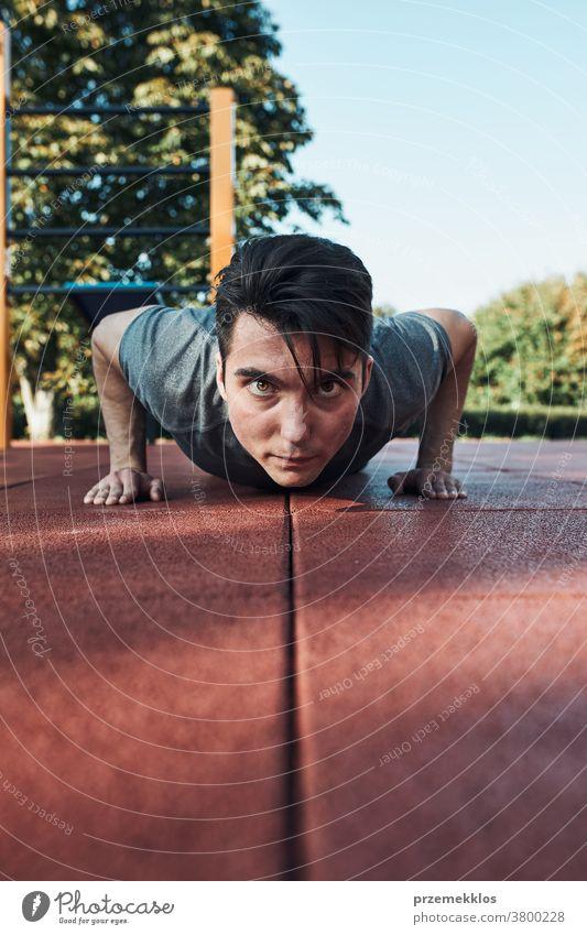 Junger Mann macht Liegestütze auf rotem Gummiboden während seines Trainings in einem modernen Trainingspark für Gymnastik calisthenics Pflege Kaukasier