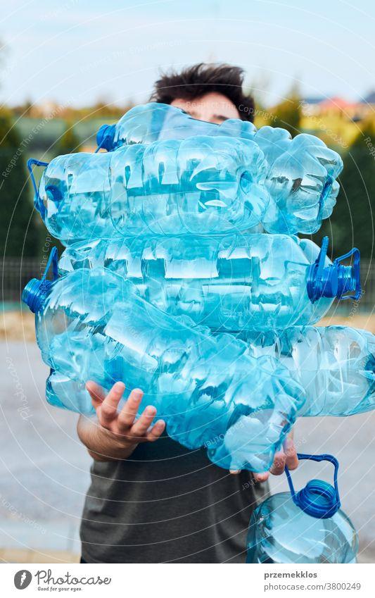 Junger Mann wirft leere gebrauchte Plastik-Wasserflaschen in den Mülleimer Behälter blau Flasche abholen sammelnd Container zerdrückt Entsorgung Ökologie Umwelt