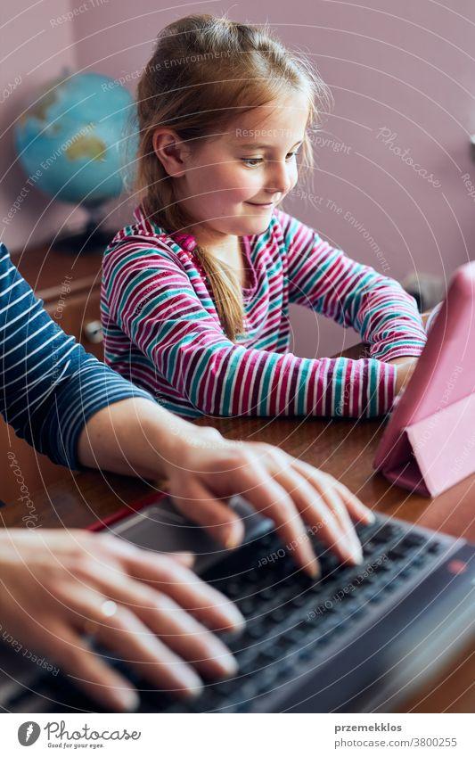 Mutter einer Frau, die während eines Video-Chat-Call-Stream-Online-Kurses auf einem Laptop von zu Hause aus ihren Job aus der Ferne erledigt, während ihre Tochter sich ein Video auf einem Tablet anschaut