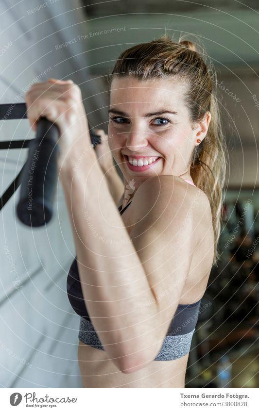 Junge glückliche Frau, die ihre Armmuskeln in der Turnhalle trainiert Fitness Übung Sport aktiv Lifestyle passen Fitnessstudio Sporthalle Gesundheit