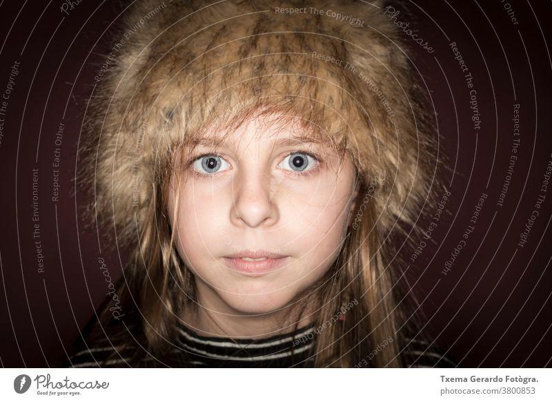 Studioporträt eines süßen Mädchens mit langen blonden Haaren, das einen Winterhut vor braunem Hintergrund trägt hübsches Mädchen Atelier-Portrait Hut Europäer