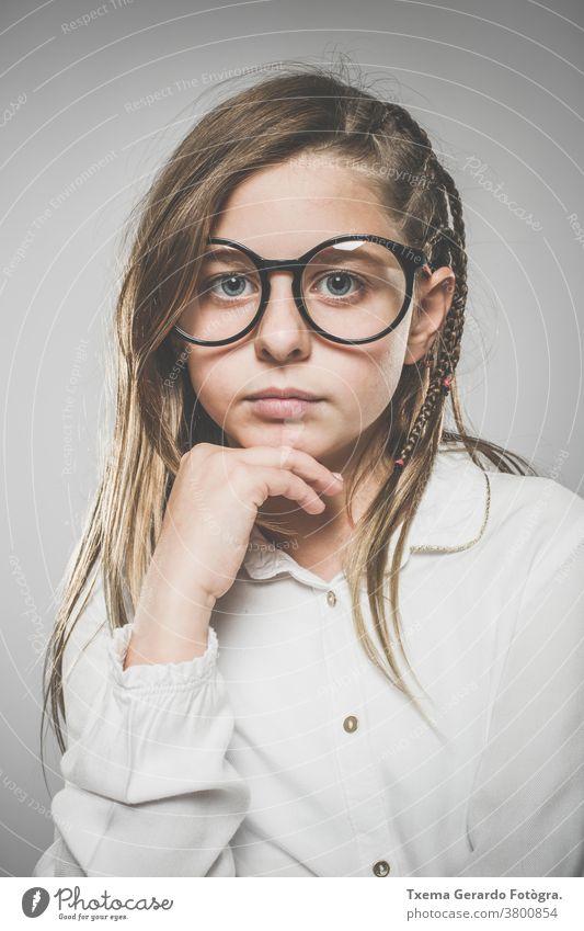 Studioporträt eines süßen Mädchens mit langen blonden Haaren und Brille vor neutralem Hintergrund hübsches Mädchen Atelier-Portrait Europäer Kaukasier