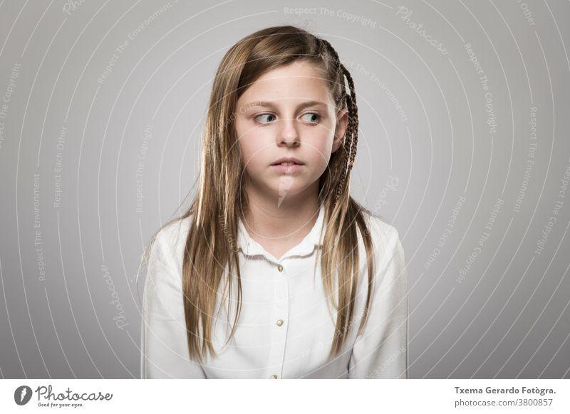 Studioporträt eines süßen Mädchens mit langen blonden Haaren, das vor neutralem Hintergrund fragend aussieht hübsches Mädchen Atelier-Portrait Europäer